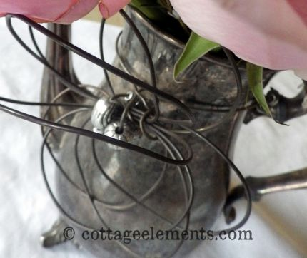 A simple silver plated coffee pot is transformed with the simple addition of a wire flower.